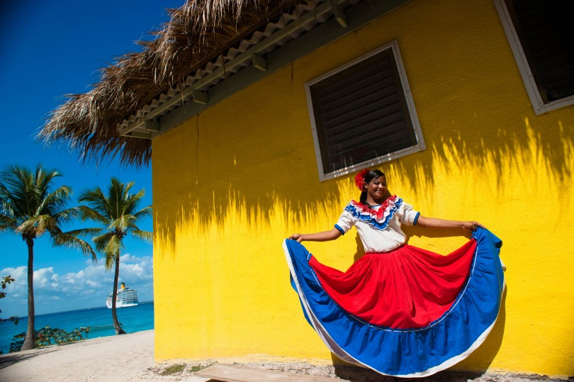 Catalina Island, Dominican Republic. A woman in traditional outfit in front of  a bungalow on a seashore (full length portrait).